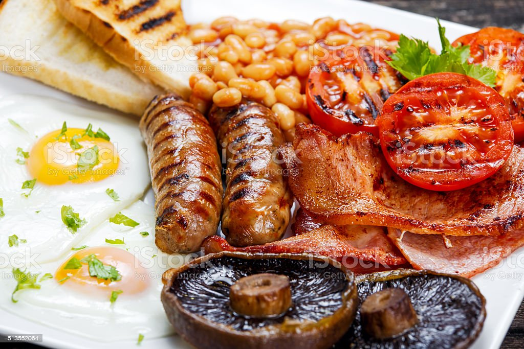 Full English breakfast with bacon, sausage, egg, beans and mushrooms stock photo