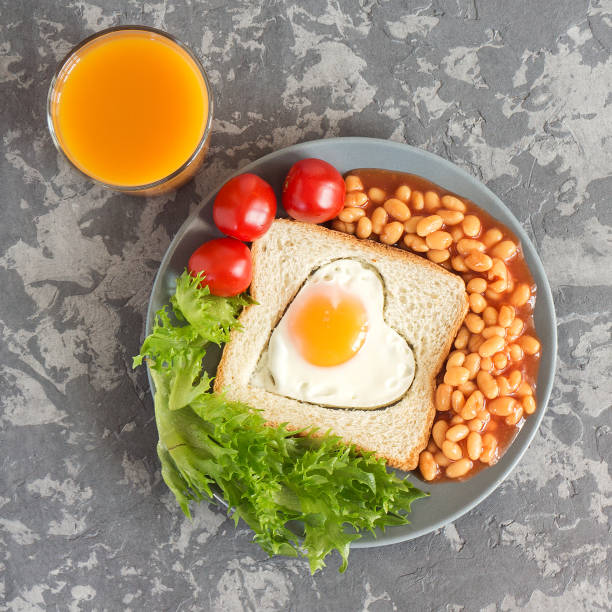 Full English Breakfast with fried eggs, beans, toasts, salad, tomatoes on gray background stock photo