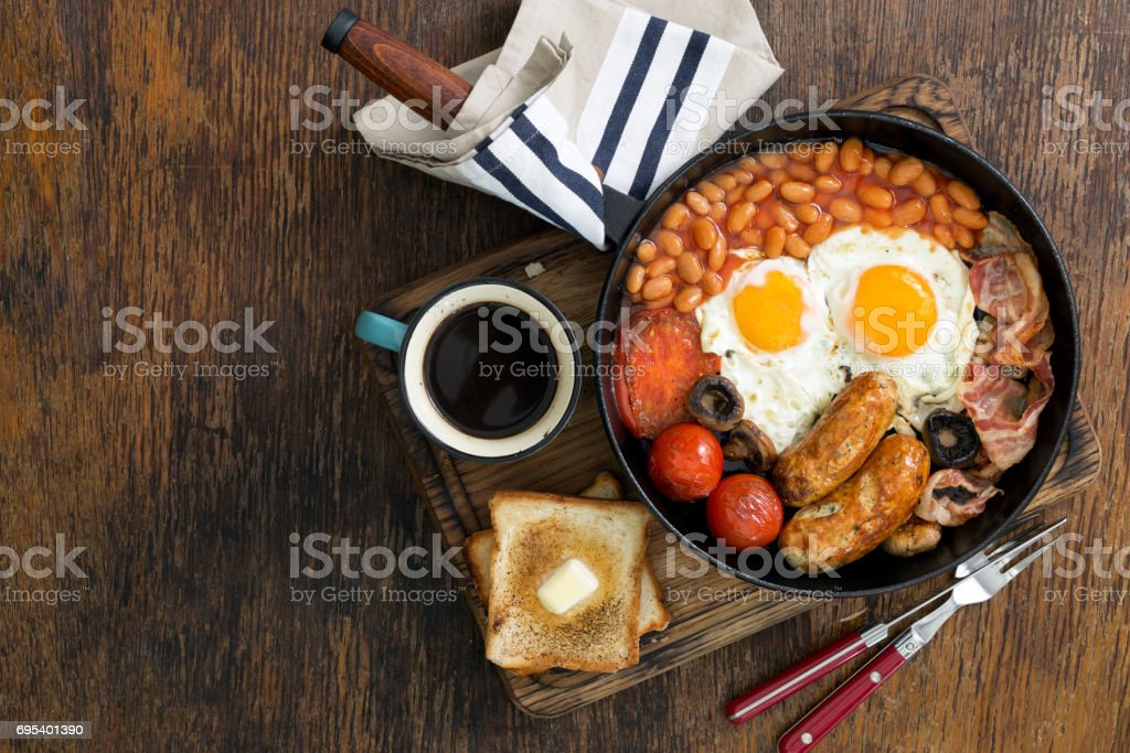Full English breakfast with sausages, bacon, fried eggs, beans, toast and cup of coffee on wooden table with copy space stock photo