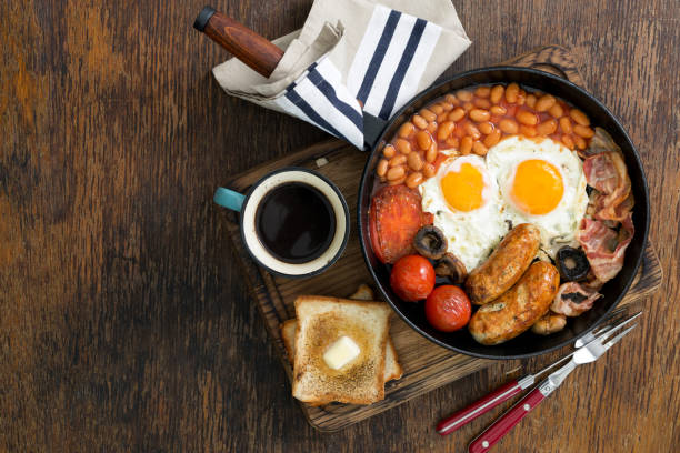 englisches frühstück mit würstchen, speck, spiegeleier, bohnen, toast und kaffee auf holztisch mit textfreiraum - gefüllte eier stock-fotos und bilder