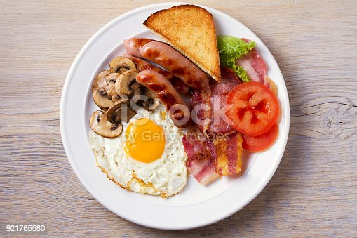 istock Full English or Irish breakfast: sausages, bacon, egg, mushrooms, tomatoes and toasts. Nutritious morning meal 921765580