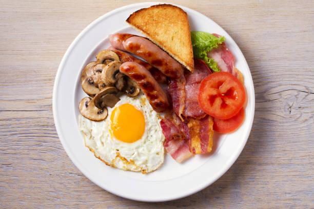 frühstück englisch oder irisch: würstchen, speck, ei, champignons, tomaten und toast. nahrhaftes frühstück - gefüllte eier stock-fotos und bilder