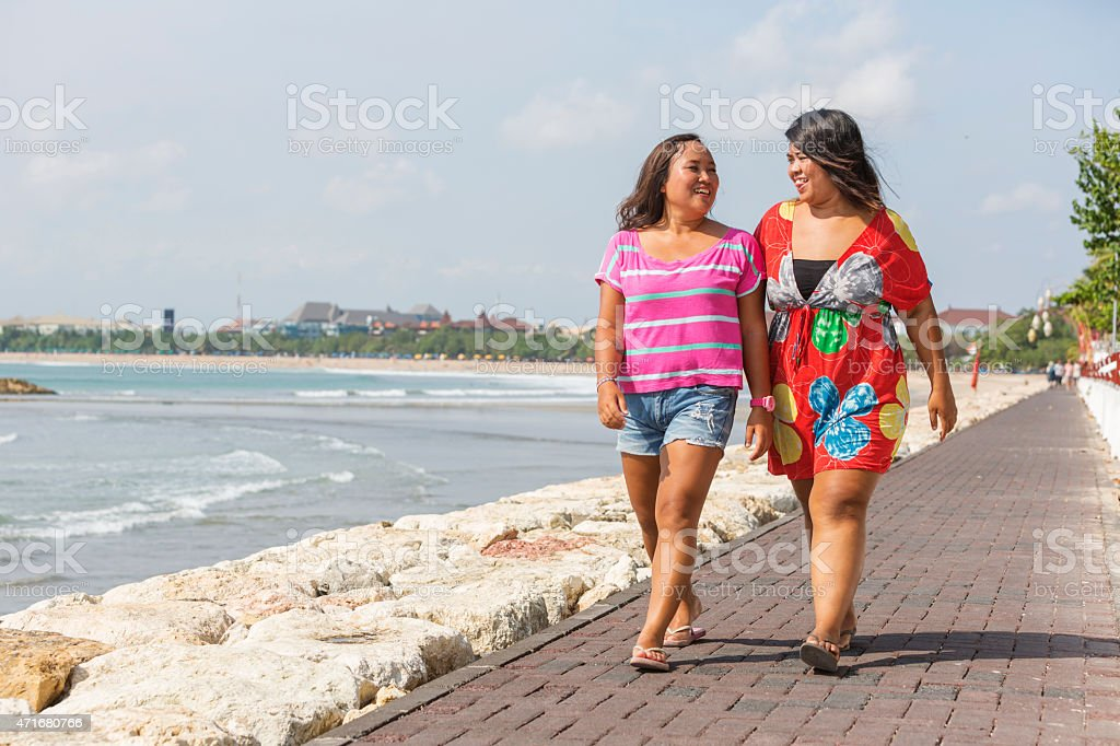 Full Figured Asian Women Walking Along the Beachfront圖像檔