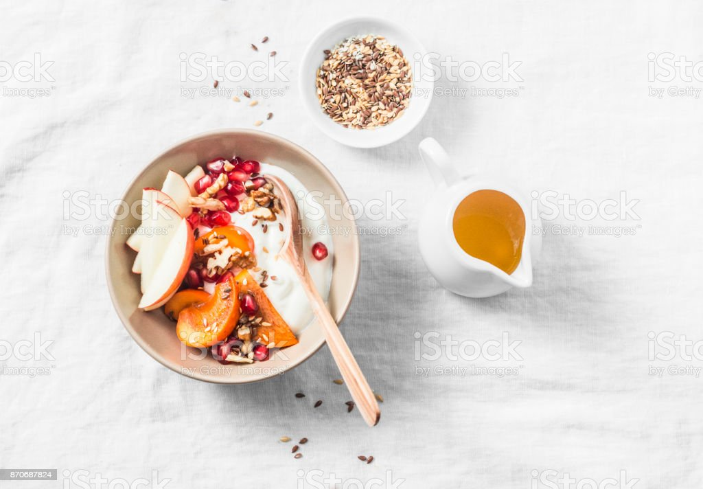 Full fruit and greek yogurt breakfast bowl. Persimmon, apple, walnuts, pomegranates and natural yogurt. Healthy food concept on light background, top view stock photo