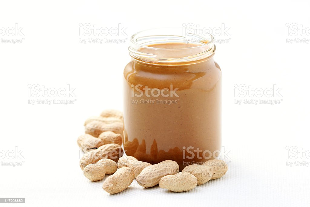 Full glass jar of peanut butter surrounded by peanuts stock photo