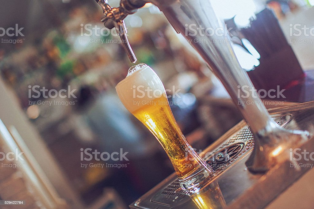 Full glass of beer under the faucet at bar stock photo
