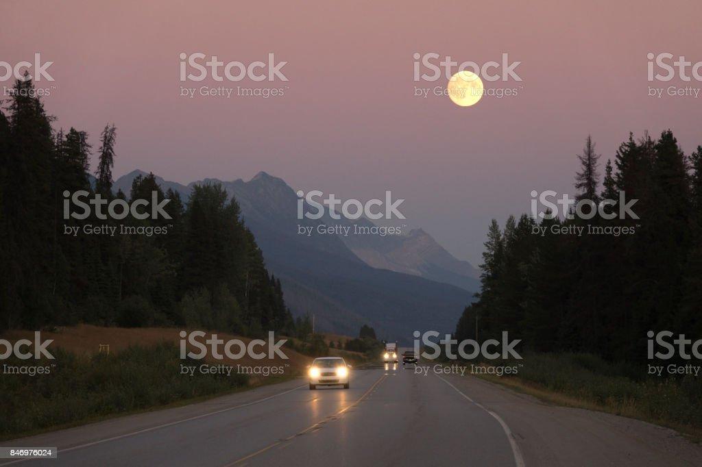 Full harvest moon over Yellowhead Highway traffic British Columbia stock photo