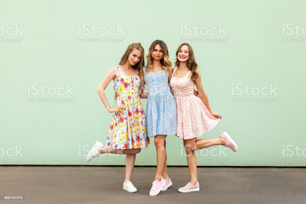 Full height image of three happy cheeky girls, best friends having fun, laughing on green background stock photo