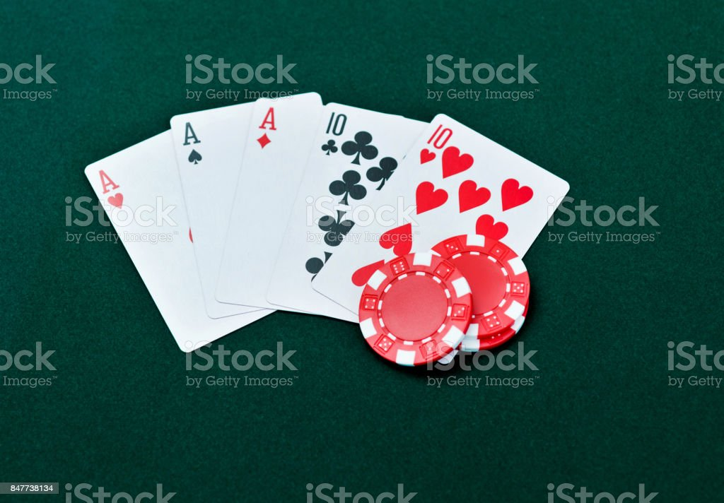 Full house and poker chips on card table stock photo