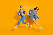 Full legs body size beautiful gorgeous adorable two lady isolated on yellow background in trendy casual street style stylish denim jeans wear glasses spectacles give heavy metal gesture play guitar