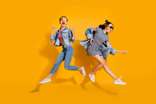 full legs body size beautiful gorgeous adorable two lady isolated on yellow background in trendy casual street style stylish denim jeans wear glasses spectacles give heavy metal gesture play guitar - женская мода стоковые фото и изображения