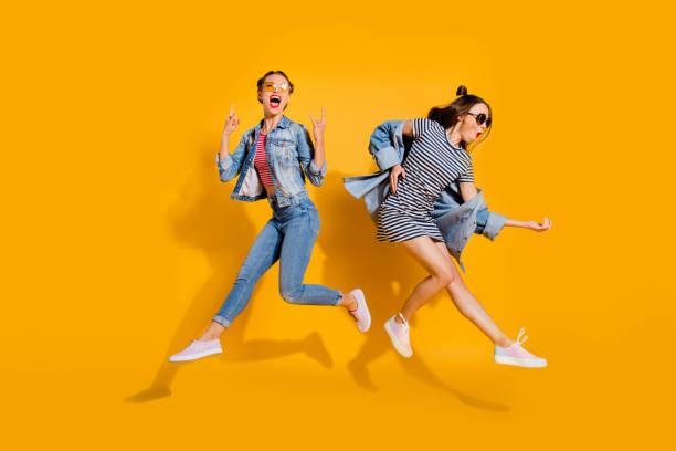 全腿身體大小美麗美麗可愛可愛的兩個女士孤立在黃色背景時尚街頭風格時尚牛仔牛仔褲戴眼鏡眼鏡給沉重的金屬手勢彈吉他 - fashion 個照片及圖片檔