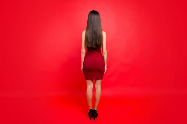 full legs body size portrait of elegant graceful glamour good-looking pretty charming lovely beautiful lady on black sharp she stand back to camera isolated on red bright background - mini dress stock photos and pictures