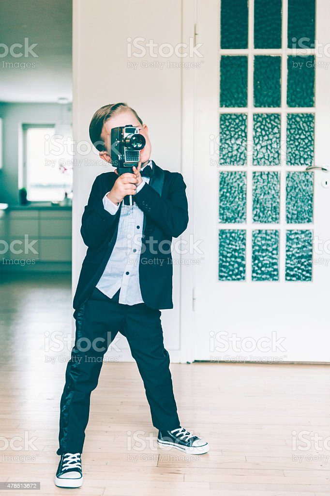Full lenght portrait of boy shooting video with retro camera stock photo