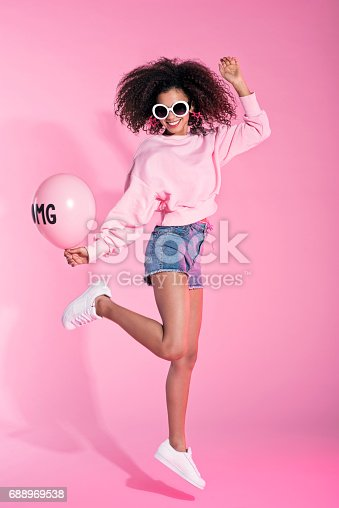 Studio portrait of young afro woman wearing denim shorts and sunglasses, holding balloon and jumping. Pink background.
