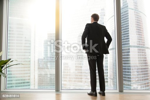 istock Full length back view of successful businessman in big city 628481614