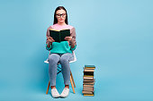 Full length body photo of focused concentrated lady in eyeglasses, specs holding thick paper book in hands isolated bright background
