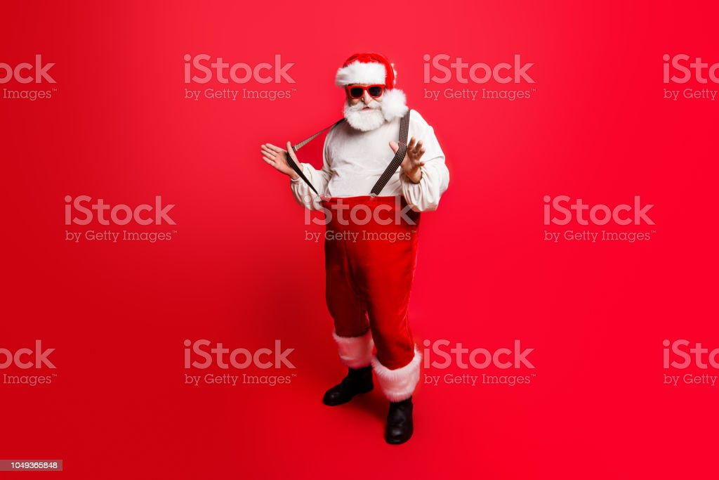 Full length body size of cheerful positive optimistic glad Santa pulling pants suspenders ready to feast festive party congrats congratulations best wishes sale discount isolated over red background stock photo