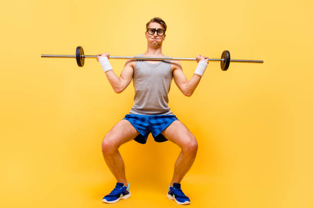 full length body size of funky caucasian guy in glasses, doing physical exercises with dumbbell, isolated over bright vivid yellow background - decrepitude stock pictures, royalty-free photos & images