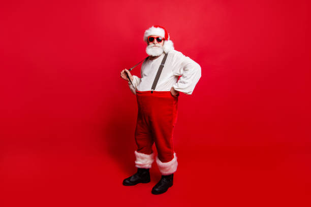 Full length body size of nice calm peaceful Santa pulling suspender preparing to feast festive party promo sale discount isolated over red background Full length body size of nice calm peaceful Santa pulling suspender preparing to feast festive party promo sale discount isolated over red background suspenders stock pictures, royalty-free photos & images