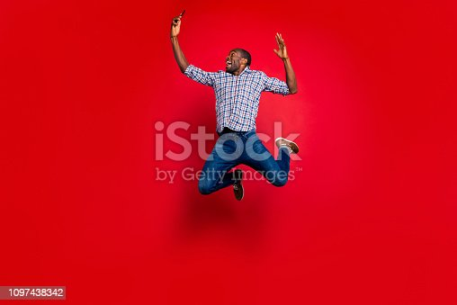 925466128 istock photo Full length body size of nice funny crazy handsome attractive cheerful cheery positive guy wearing checkered shirt holding in hands cell reading text isolated over bright vivid shine red background 1097438342