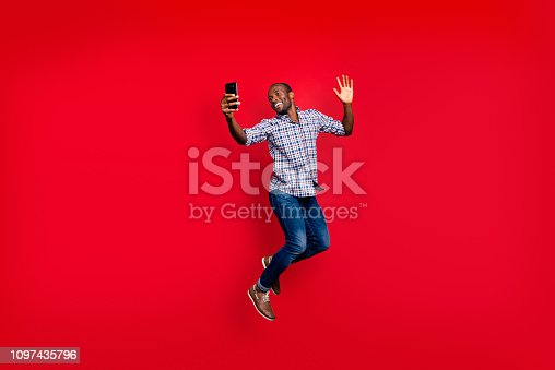 istock Full length body size of nice funny crazy handsome cheerful optimistic guy wearing checkered shirt holding in hands cell waving hi hello isolated on bright vivid shine red background 1097435796
