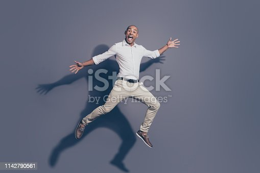 925466128 istock photo Full length body size photo amazing dark skin he him his macho shake hands arms up air jump high great mood playful crazy fooling around wear white shirt pastel pants isolated grey background 1142790561