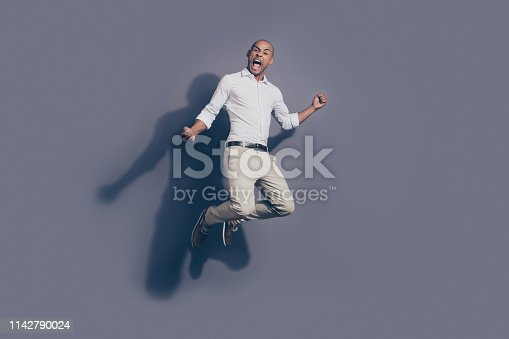 925466128 istock photo Full length body size photo amazing yelling loud dark skin he him his macho handsome jump high true fan cheerleader football baseball basketball wear white shirt pastel pants isolated grey background 1142790024