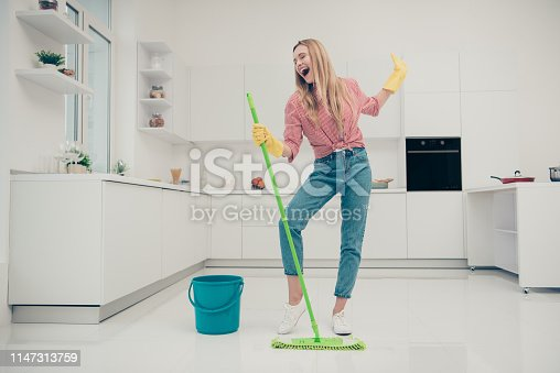 1081403344 istock photo Full length body size photo beautiful amazing funky she her lady wash white floor housemaid karaoke day singing mop crazy movement wear jeans denim casual plaid checkered shirt bright light kitchen 1147313759