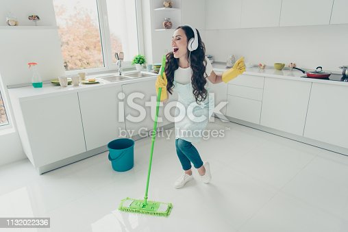 1081403344 istock photo Full length body size photo beautiful attentive hardworking pleasant duties she her lady house ear flaps head playlist audio wear jeans denim casual t-shirt covered cute apron bright light kitchen 1132022336