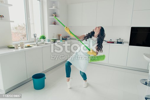 1081403344 istock photo FUll length body size photo beautiful busy nice duties she her lady indoors sing songs dancing washing supplies housemaid wear jeans denim casual t-shirt covered by cute apron bright light kitchen 1132023937
