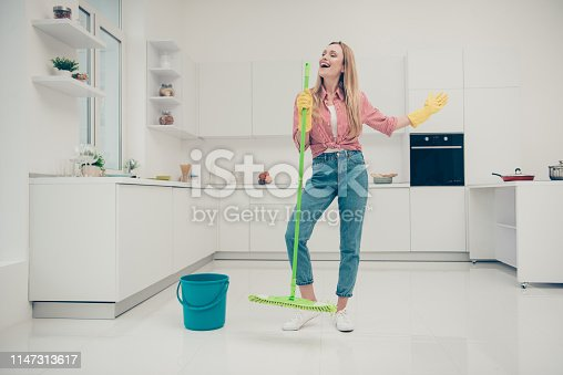 1081403344 istock photo Full length body size photo beautiful busy nice duties she her lady wash white floor funky housemaid karaoke day singing mop crazy wear jeans denim casual plaid checkered shirt bright light kitchen 1147313617