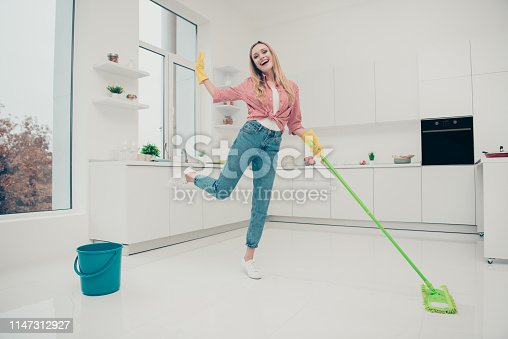 1081403344 istock photo Full length body size photo beautiful domestic duties she her lady wash white shiny floor dance listen playlist audio sound track wear jeans denim casual checkered plaid shirt bright light kitchen 1147312927