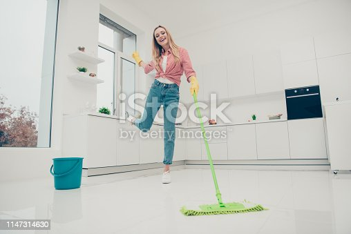 1081403344 istock photo Full length body size photo beautiful domestic duties she her lady rhythms motion wash white shiny floor listen playlist audio sound wear jeans denim casual checkered plaid shirt bright light kitchen 1147314630