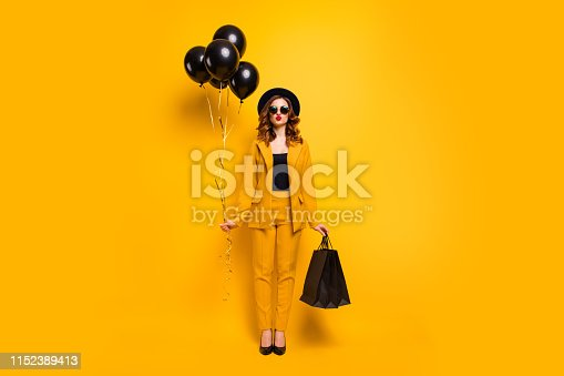 Full length body size photo beautiful she her lady send air kiss carry packs perfect look festive guest birthday presents balloons wear specs formal-wear costume suit isolated yellow bright background.