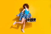Full length body size photo beautiful she her lady wavy styling curls old-fashioned tape recorder dancing excited wear specs casual jeans denim shirt shorts tank top clothes isolated yellow background.