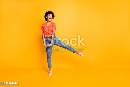 Full length body size photo of cheerful cute nice rejoicing overjoyed african youngster, seeing her favorite goods discounted wearing jeans denim sneakers isolated vivid color background