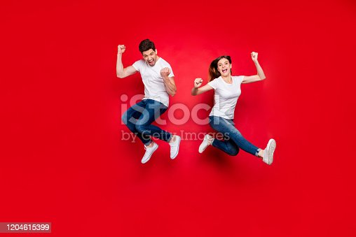 Full length body size photo of cheerful positive jumping excited rejoicing, overjoyed girlfriend boyfriend wearing jeans denim white t-shirt footwear screaming yes yeah isolated vivid color background