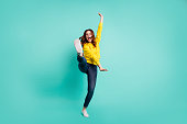 Full length body size photo of crazy ecstatic overjoyed cheerful cute nice childish girl wearing jeans denim footwear screaming loudly, training fight skills isolated over teal vivid color background