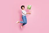 Full length body size photo of excited crazy funky funny cheerful cute, childish girlfriend catching gift box jumping in jeans denim striped sweater isolated over pastel pink color background