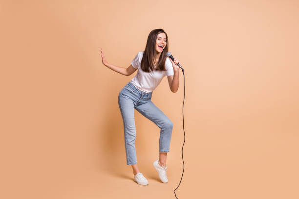 Full length body size photo of female pop star singing song keeping mic dancing on stage isolated on pastel beige color background stock photo