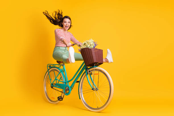 Full length body size photo of funky girl riding bicycle keeping legs up screaming isolated on bright yellow color background stock photo