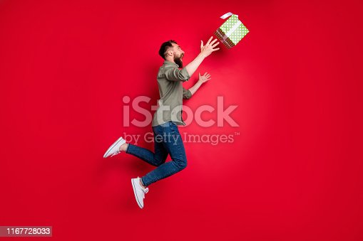 Full length body, size photo of man trying to catch his prize gift while isolated with red background