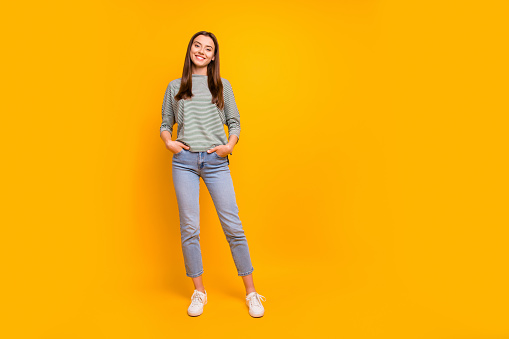 Full length body size photo of nice cute encouraged girlfriend with, her hands in pockets while isolated with yellow background