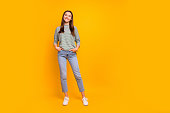 istock Full length body size photo of nice cute encouraged girlfriend with her hands in pockets while isolated with yellow background 1166389425