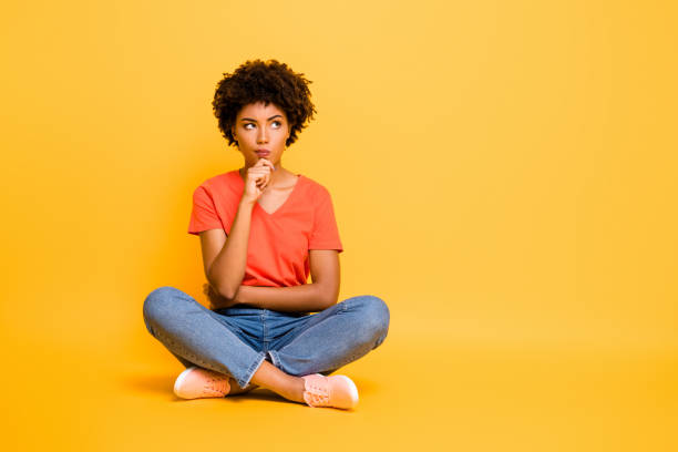Full length body size photo of pensive solving deciding minded girlfriend sitting with her legs crossed wearing jeans denim t-shirt touching her chin isolated over yellow vivid color background stock photo