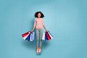 Full length body size photo of stretching jumping excited crazy rejoicing girl black friday packages in striped t-shirt trousers pants, footwear isolated over blue pastel color background