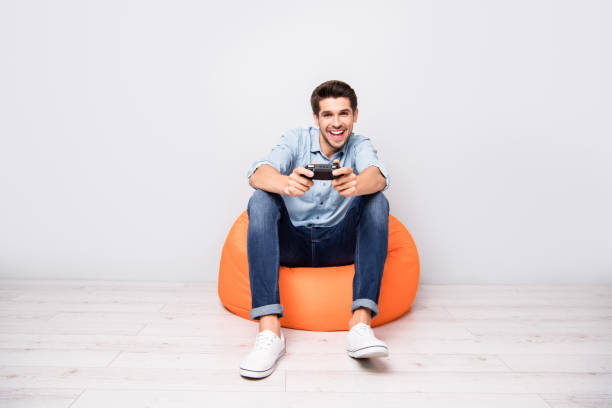full length body size photo of trendy man addicted to playing video games wearing white sneakers holding joy stick with hands isolated over grey color background - man joystick imagens e fotografias de stock