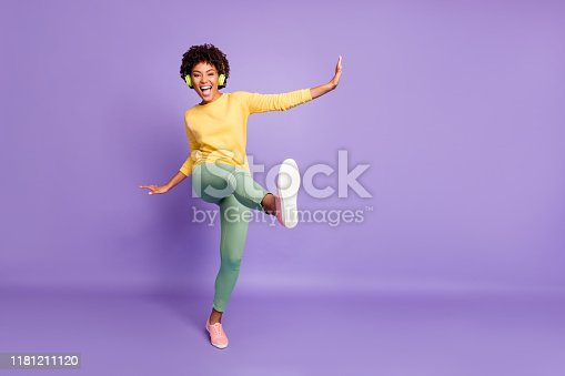 Full length body size photo of wavy cheerful excited ecstatic overjoyed, shouting girlfriend dancing listening to music pretending to be kicking with leg near empty space isolated over violet color pastel background