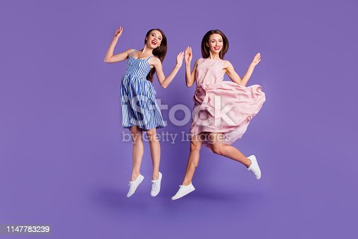 Full length body size photo two people beautiful funky she her models chic ladies jumping high best cheerleaders fans celebrating breakthrough wear summer dresses isolated purple violet background.